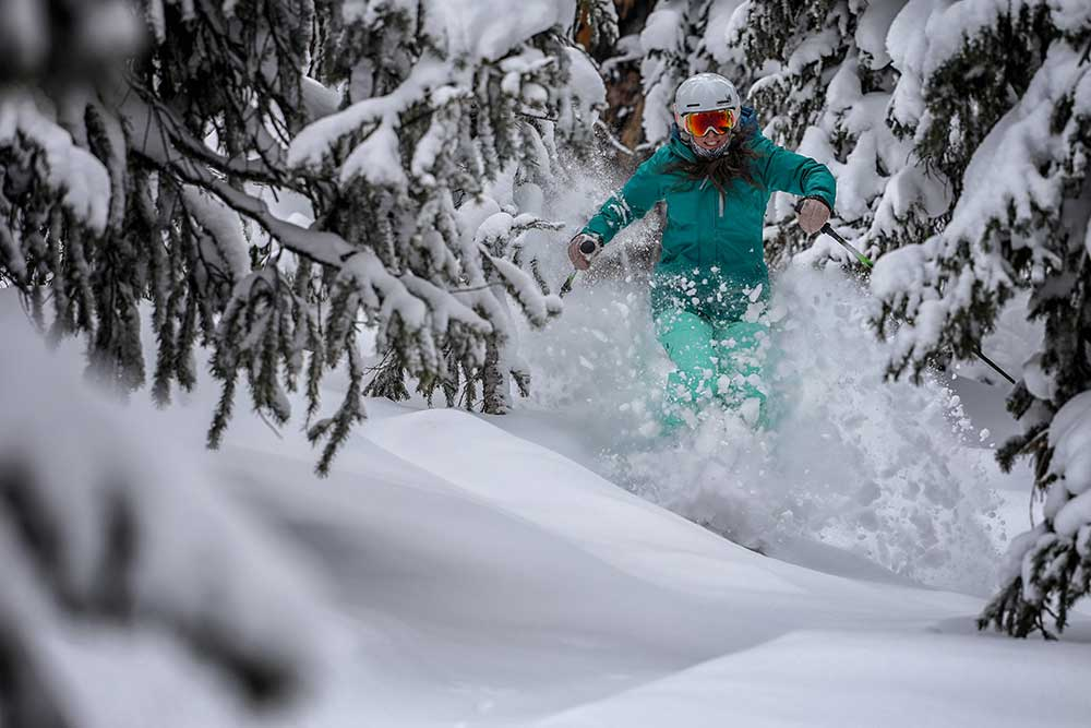 A skier makes her way through the trees skiing in powder at Copper Mountain