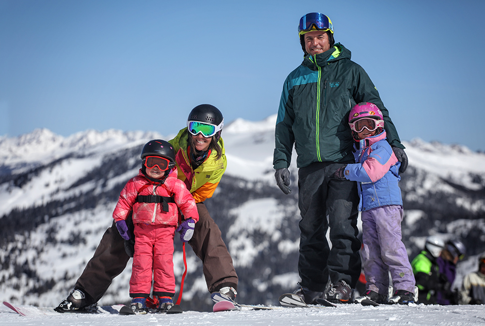 A family of four smiling while skiing on a sunny day at Copper Mountain in the Colorado Rocky Mountains