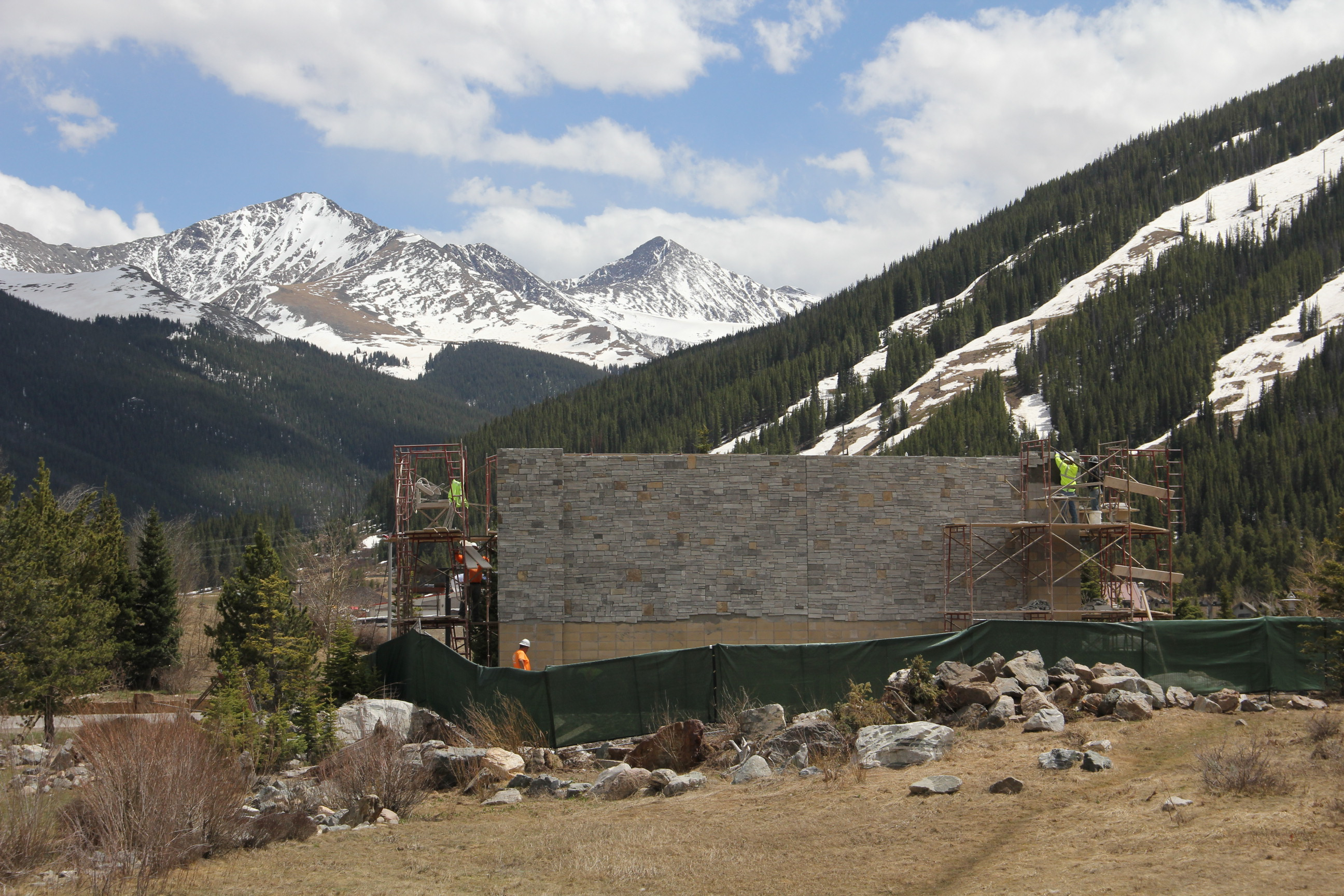 A view of the Copper Mountain entry monument being built, tall rock formation with view of the mountains behind it