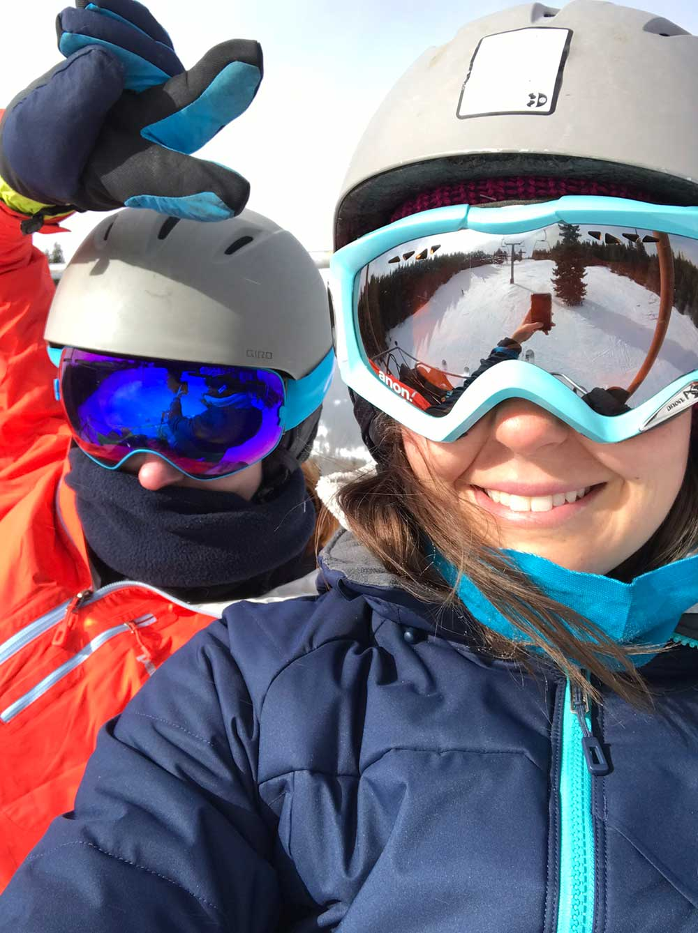 Two friends pose in helmets and goggles while skiing at Copper Mountain