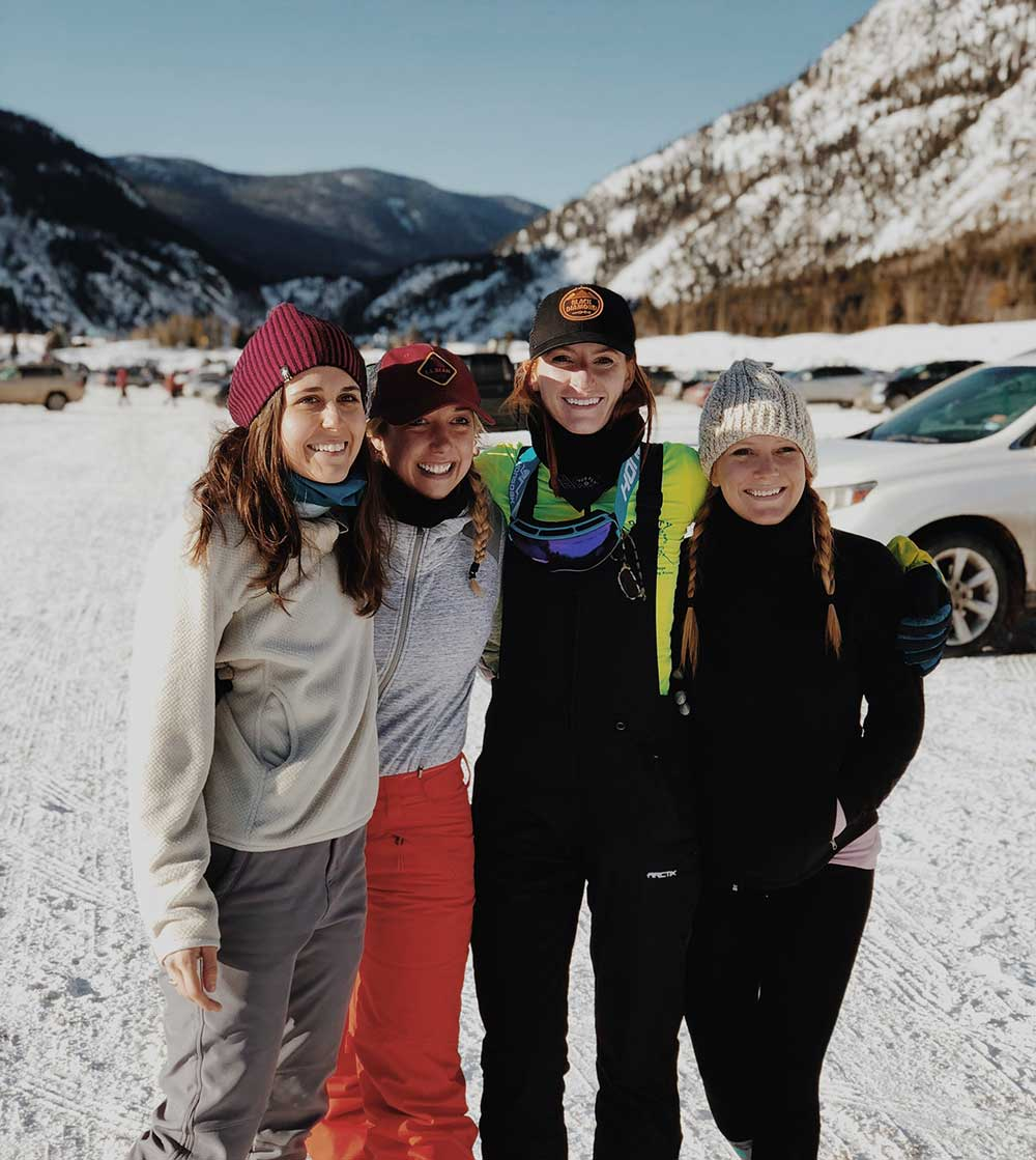 Friends pose for photo while getting ready for skiing in parking lot at Copper Mountain