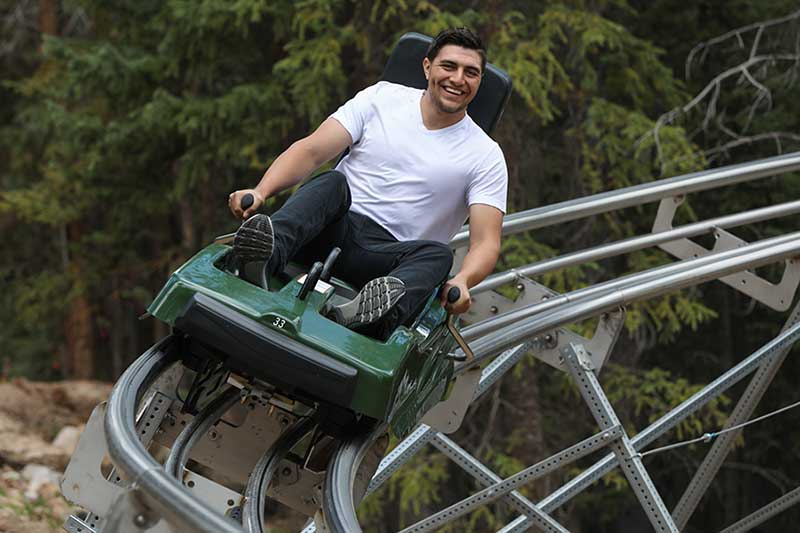 A man rolls down the track on the Rocky Mountain Coaster at Copper Mountain